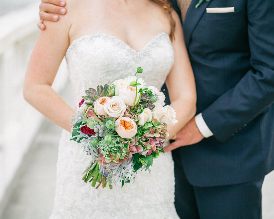 Bride Holding Blush, Pink, and Green Wedding Bouquet with Roses and Succulents