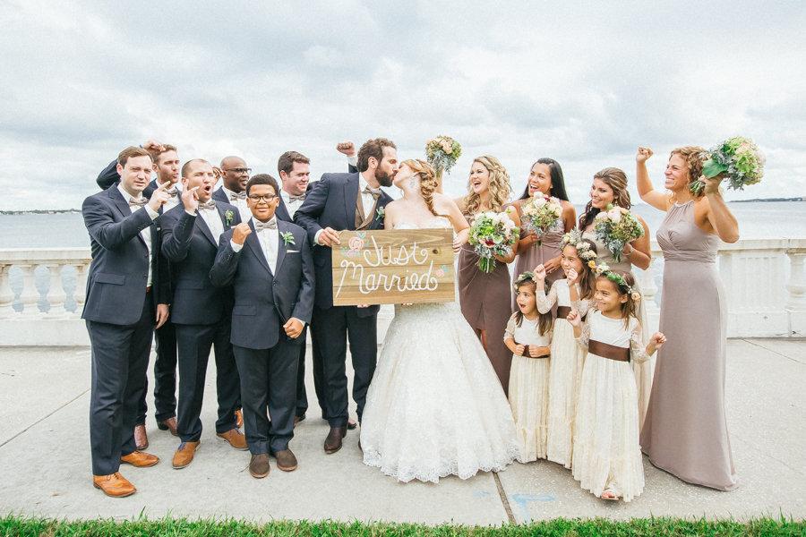 Bridal Party Wedding Portrait Celebrating on Bayshore Boulevard Holding Just Married Sign | Tampa Wedding Photographer Rad Red Creative
