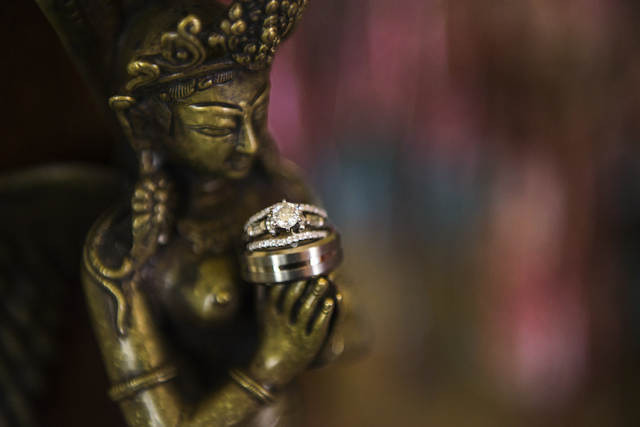 Bride and Groom Wedding Bands and Engagement & Wedding Ring Detail on Buddha Statue