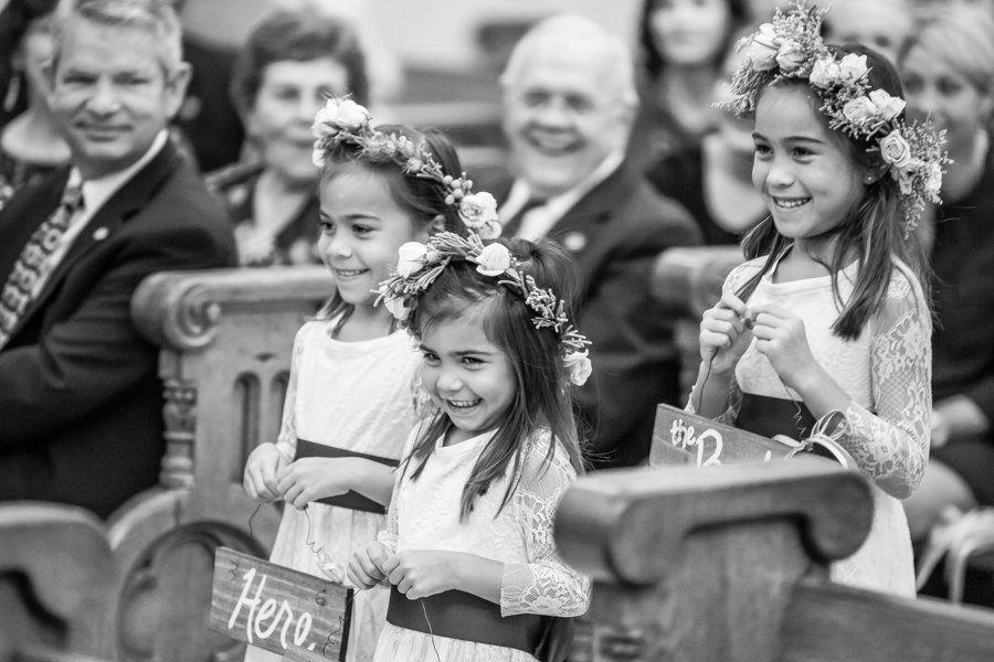 Flower Girls Holding Here Comes the Bride Signs Walking Down the Wedding Aisle