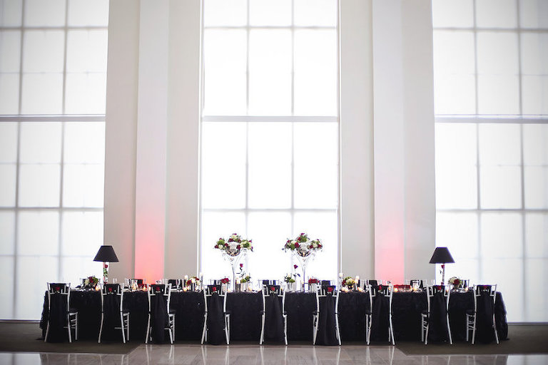 Downtown Tampa Wedding Reception with Black Linen, White Chiavari Chairs, and Red, Ivory and Green Centerpieces at the Vault | Tampa Wedding Photographer FotoBohemia