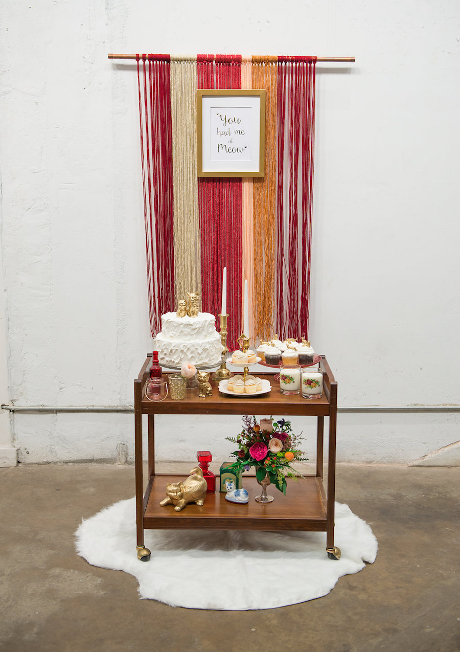 Cat Themed Tampa Bay Wedding Reception Cake and Dessert Bar Cart with White Fur Accent and Yarn Backdrop at Tampa Bay Wedding Venue Rialto Theatre | Fur Rental from Tampa Bay Wedding Rental Company Kate Ryan Linen | Wedding Cake from Tampa Bay Bakery Cakes Tampa | Styled by Tampa Bay Wedding Designer Ever After Vintage Weddings | Tampa Bay Wedding Photographer Artful Adventures Photography