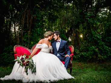 Bride in Amsale Wedding Dress from Blush Bridal Sarasota with Deep Red Burgundy Wedding Bouquet with Greenery on Red Vintage Couch Chaise | Southern Inspired Outdoor Wedding Reception Decor Styled Shoot