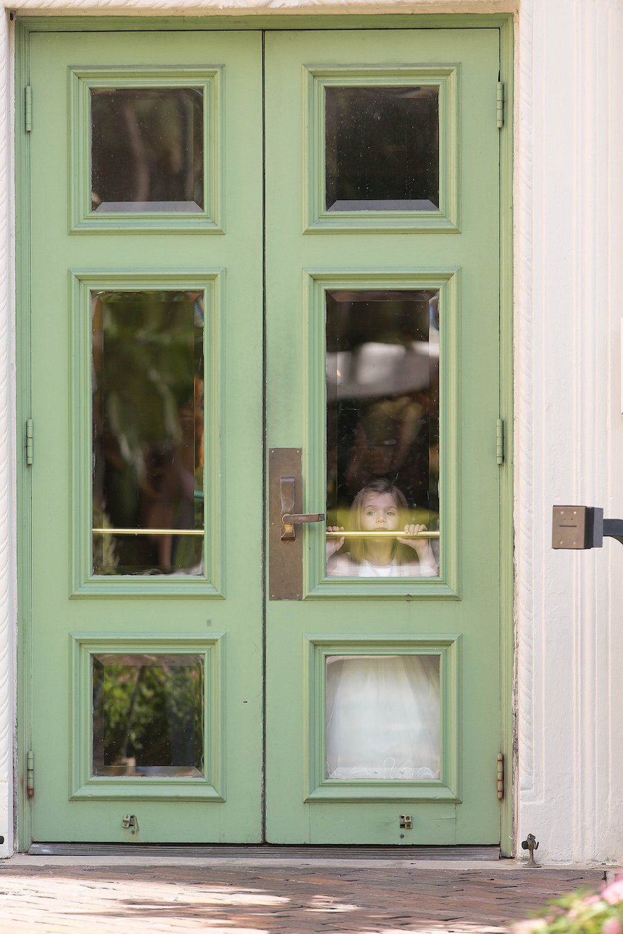 Flower Girl on Wedding Day Peering out Window| Photo by Tampa Bay Wedding Photographer Kristen Marie Photography