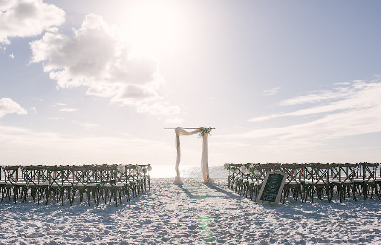 Beach Wedding With Wooden Chairs And Bamboo Arch Sunset Resort Siesta Key