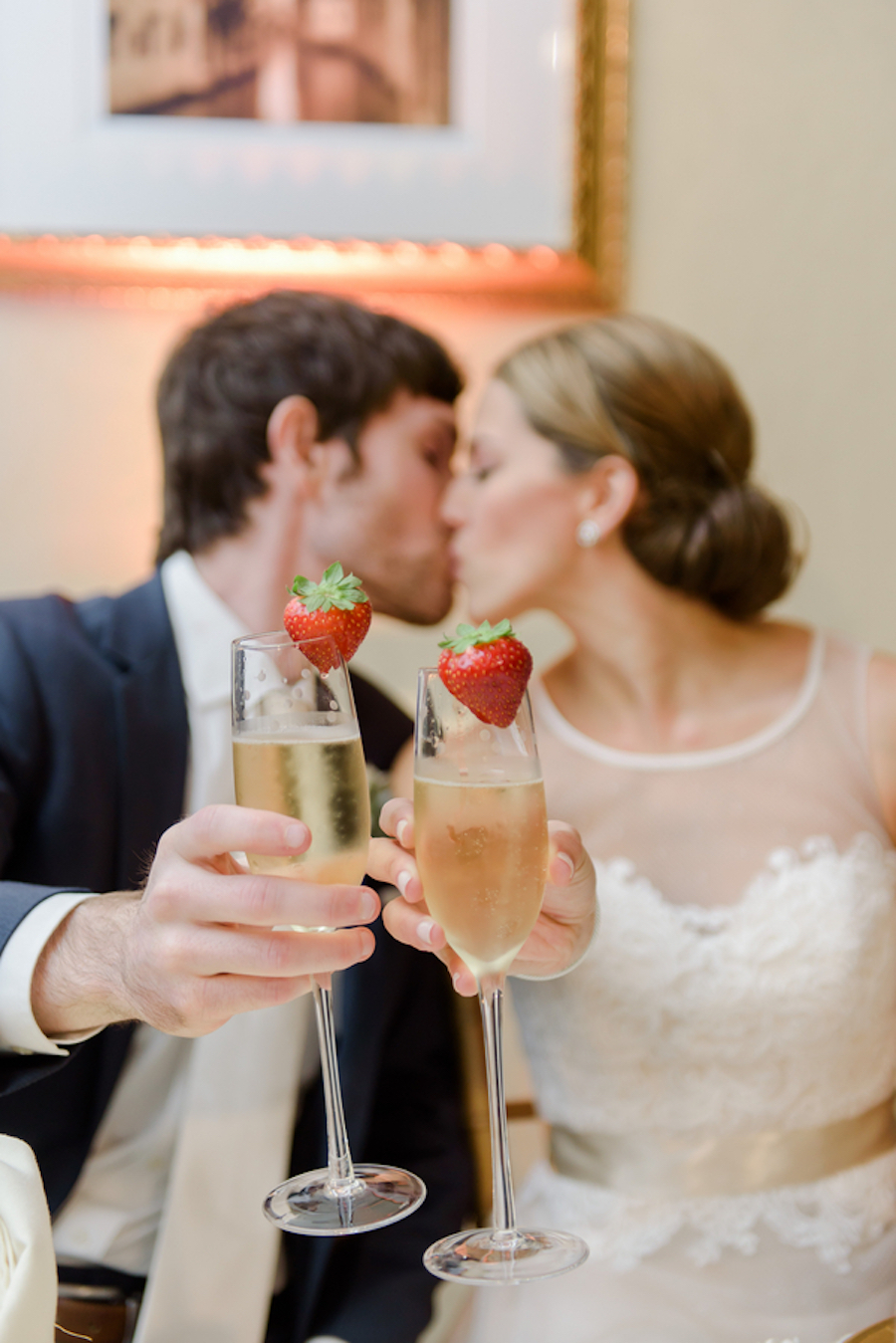 Bride and Groom Portrait Kissing Holding Champagne Glasses with Strawberries