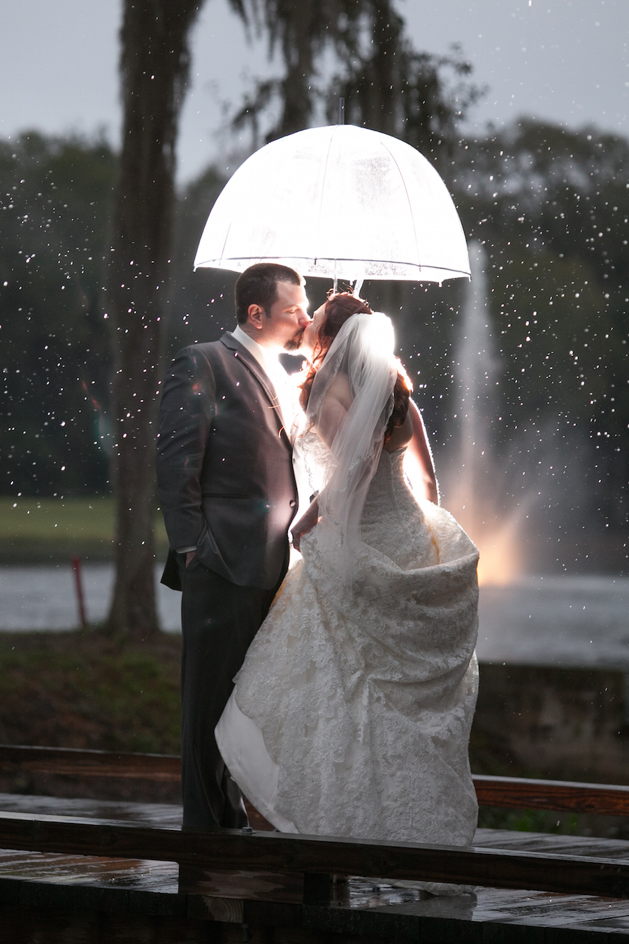Bride and Groom Wedding Portrait in the Rain with Umbrella by Tampa Bay Wedding Photographer Carrie Wildes Photography