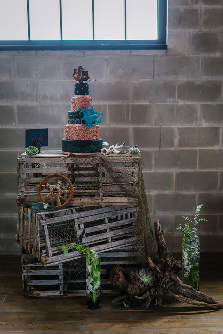 Ybor City Wedding Cake Display Table with Black and Gold Nautical Inspired Wedding Cake With Pirate ship and Octopus on Wooden Fishing Crates | Coppertail Brewing Co