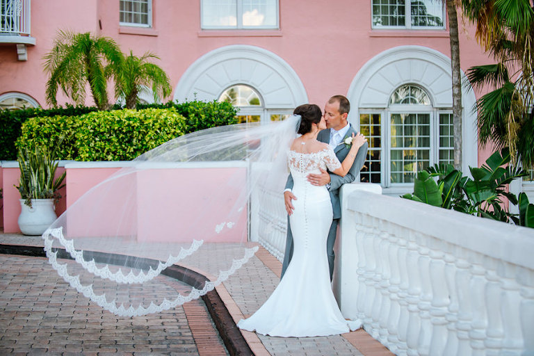 Bride and Groom, Outdoor St. Petersburg Wedding Portrait at the Loews Don CeSar | Off the Shoulder, Lace, White Wedding Gown and Lace Chapel Length Veil