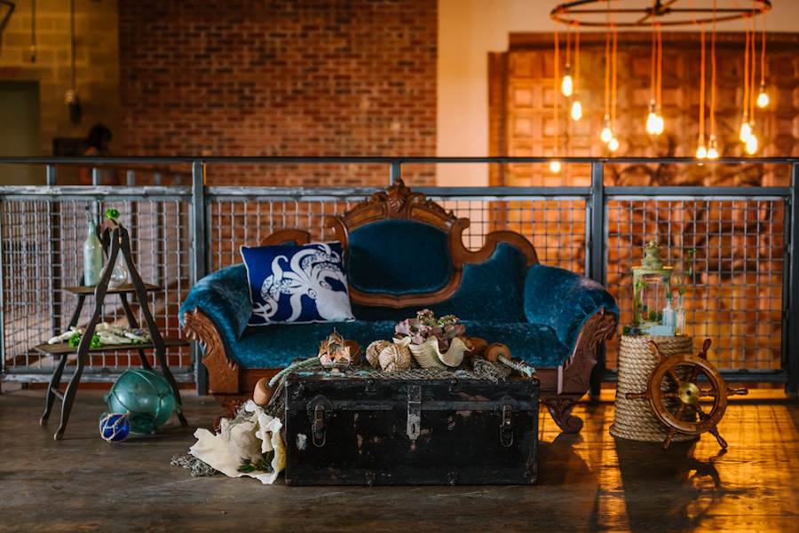 Ybor City Nautical Inspired Sitting Area and Blue Velvet Settee, Antique Black Wooden Chest, Buoy, Ship Rope, Ship Wheel and Sea Glass | Coppertail Brewing Co