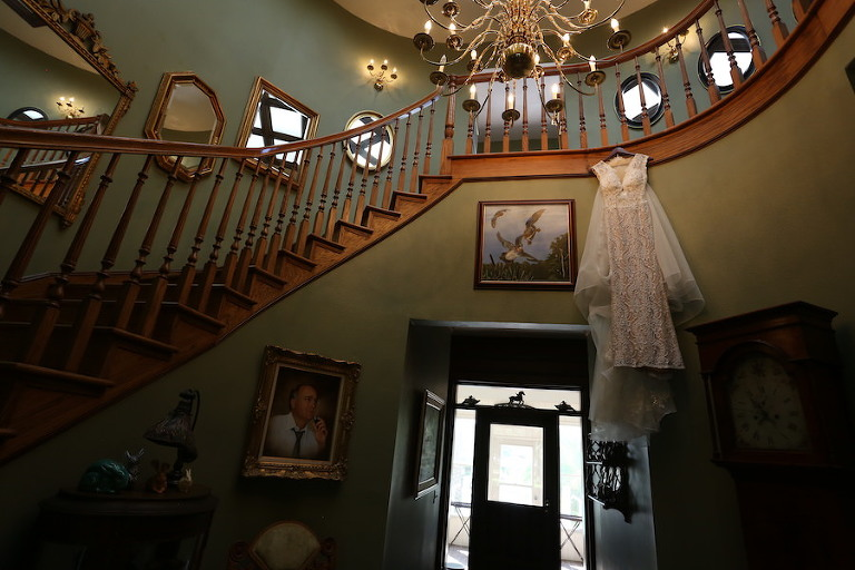 Getting Ready Portrait: Ivory, Lace Bridal Wedding Gown Hanging on Staircase | Lakeland Wedding Venue Rocking H Ranch