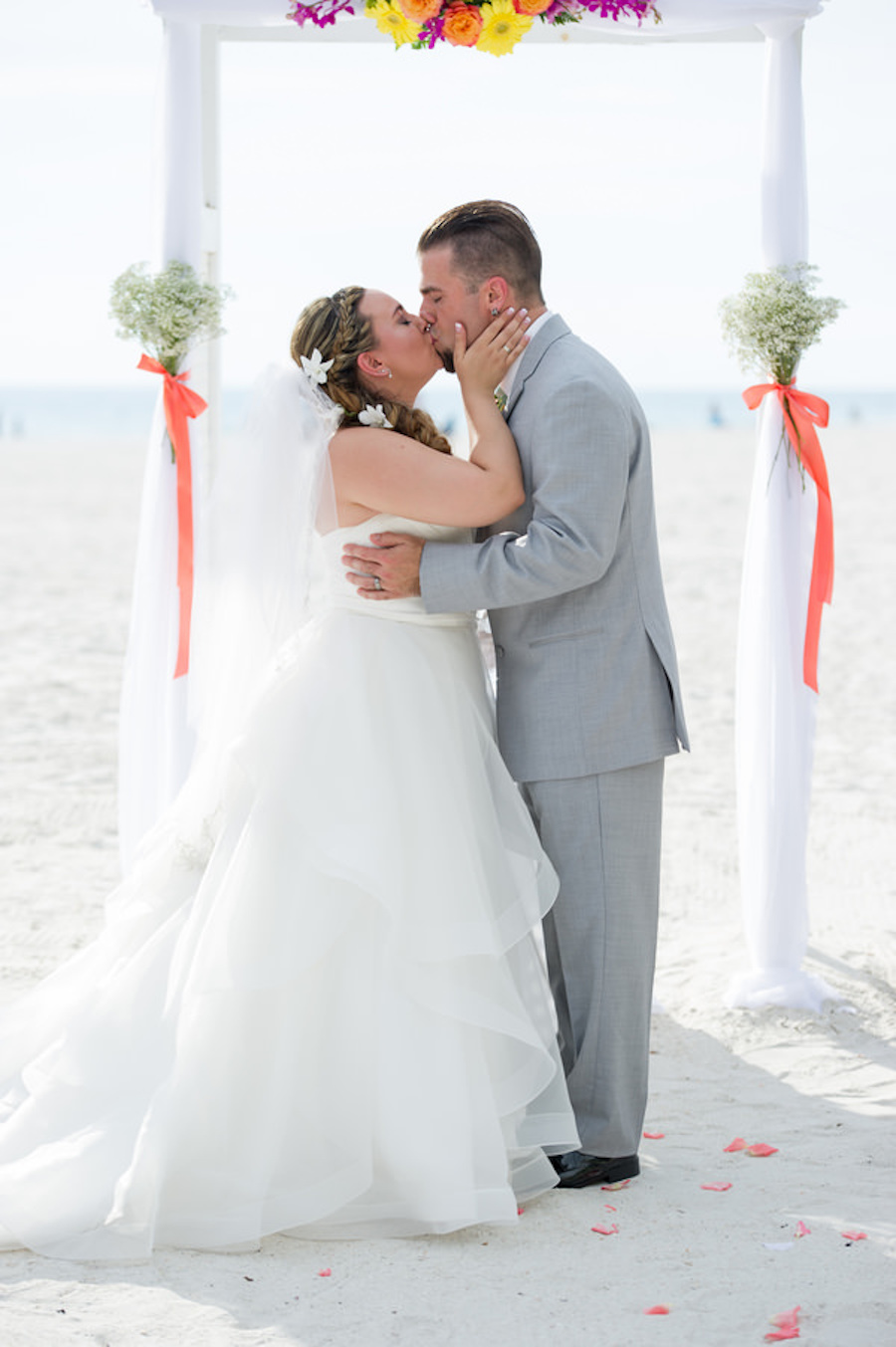 St. Pete Beach Wedding Ceremony First Kiss Portriat with Bride in Strapless White Wedding Ballgown and Groom with Grey Suit  St. Pete Wedding Photographer Andi Diamond Photography