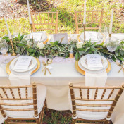 Wedding Reception Tablescape with Lush Greenery Table Runner with Gold Candle Sticks with Gold Chargers with Gold Silverware with Ivory Linens with Gold Chiavra| Andrea Layne Floral Design | Kate Ryan Custom Linens