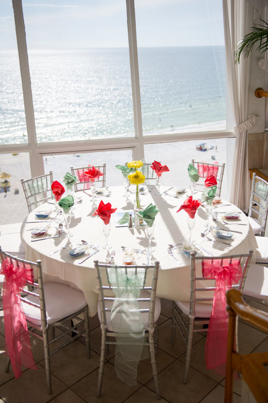 Wedding Reception Tablescape with Chiavari Chairs with Organza Pink and Mint Green Sashes and Colorful Coral and Mint Napkins with Yellow Centerpieces   St. Pete Wedding Photographer Andi Diamond Photography   St. Pete Beach Wedding Venue The Grand Plaza Hotel