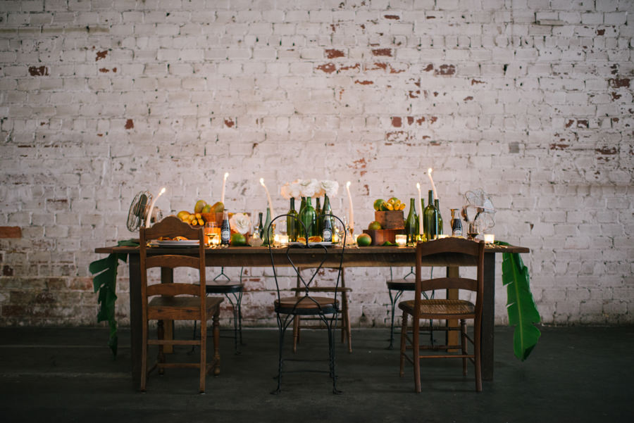 Caribbean, Eco-Friendly Wedding Reception Decor with Farmhouse Table, Wooden and Metal Chairs, Palm Leaves, Fresh Fruit, and White Flowers in Glass Bottles | Tampa Wedding Venue Rialto Theatre