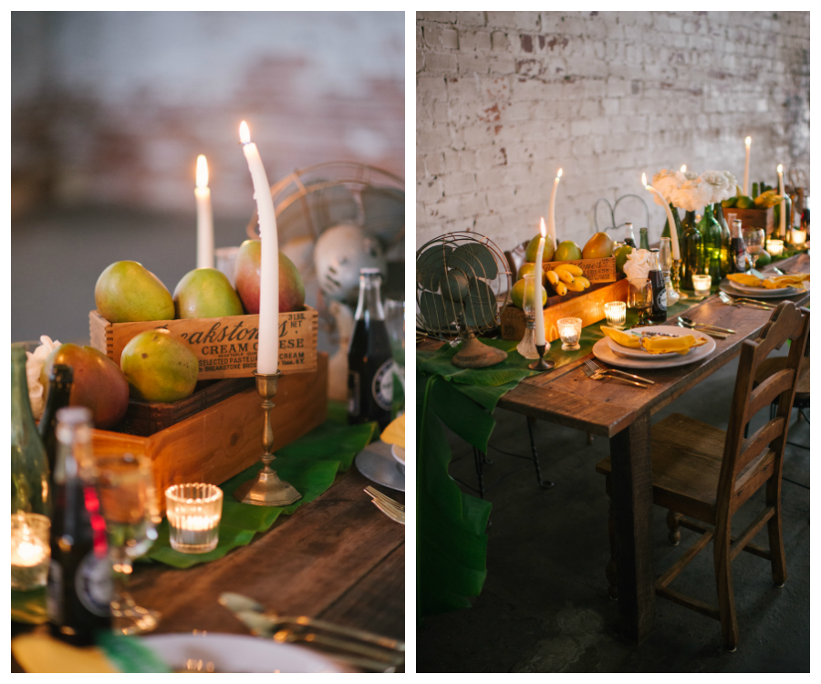 Caribbean and Eco Friendly Inspired Wedding Reception Table Decor with White Flowers in Upcycled Glass Bottles, Palm Leaves, Fresh Organic Fruit, and Melted Candles on a Farmhouse Table with Yellow Napkins