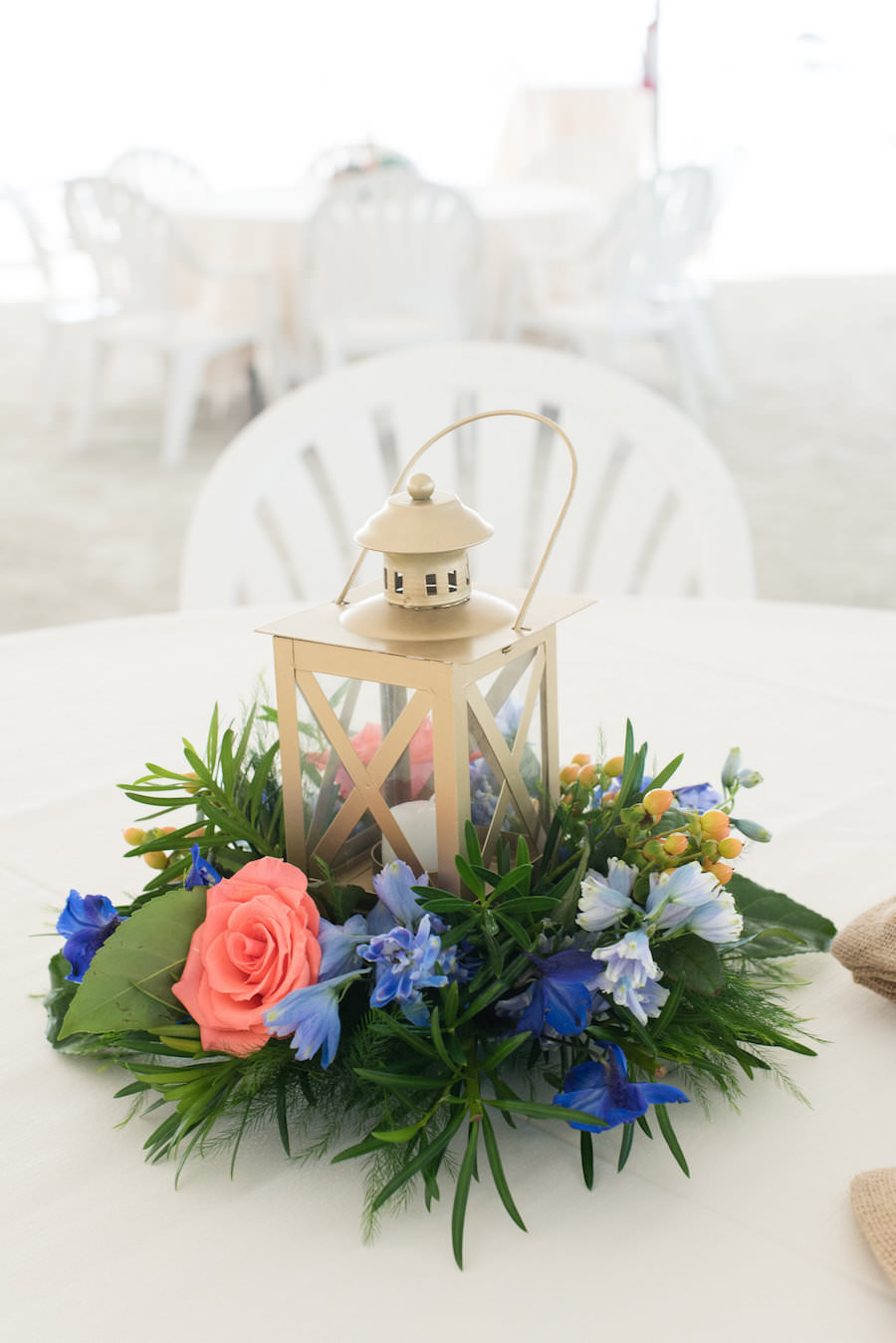 Beach Wedding Reception Table Decor with Gold Lanterns with Lush Greenery and Pink and Blue Flowers   Clearwater Wedding Photographer Caroline and Evan Photography
