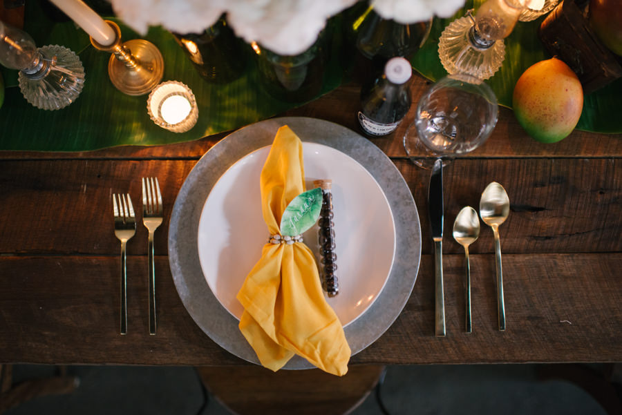 Caribbean and Eco Friendly Inspired Wedding Reception Table Decor Palm Leaves, Fresh Organic Fruit, on a Farmhouse Table with Yellow Napkins