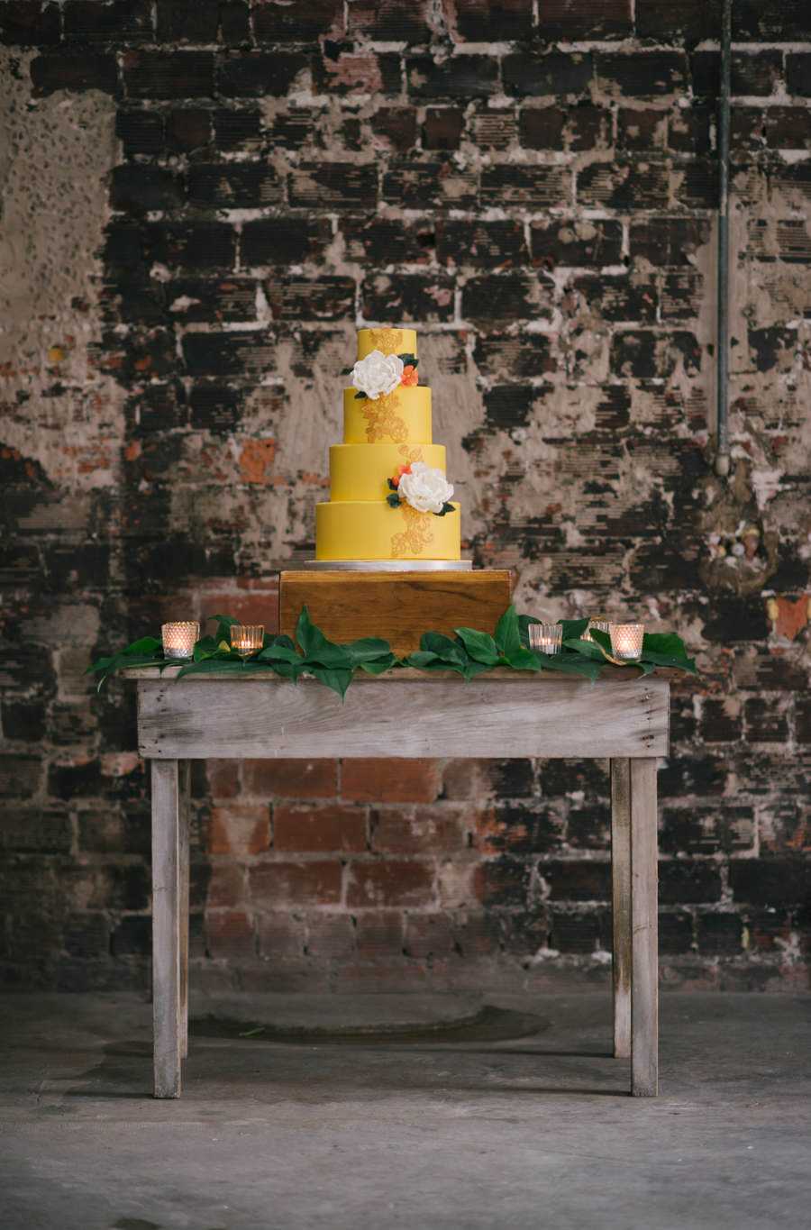 Caribbean Inspired, 4- Tiered Round Wedding Cake on Wooden Table with Yellow Fondant and Gold Design Detailing Accented with White Flowers | Tampa Wedding Venue Rialto Theatre