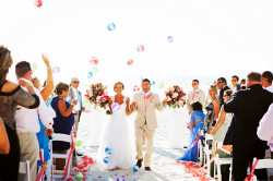 Beach, Outdoor Wedding Ceremony, Bride and Groom Walking down Aisle and Guests Throwing Beachballs | Clearwater Beach Wedding Photographer Limelight Photography