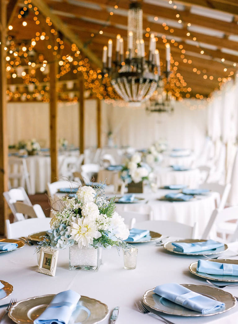 Wedding Reception Tablescape With Champagne Gold Charger Plates And Light Blue Linen Napkins Low White