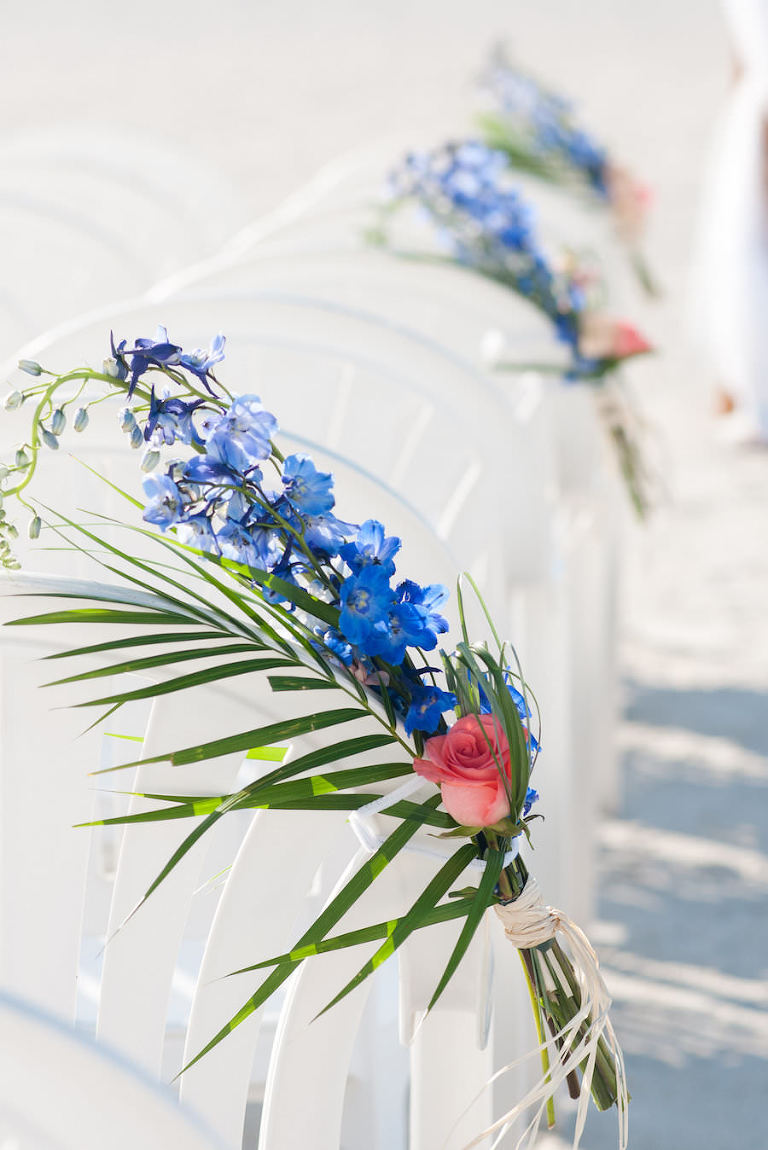 Wedding Ceremony Decor with Palm Tree Leaves, Pink Roses and Blue Flowers on White Beach Chairs