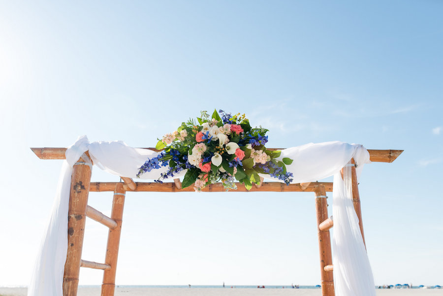 Florida Beach Wedding Ceremony Bamboo Arch Decor with Palm Tree Leaves, Pink Roses, Blue Flowers and White Lillies with White Draping Fabric   Clearwater Wedding Photographer Caroline and Evan Photography