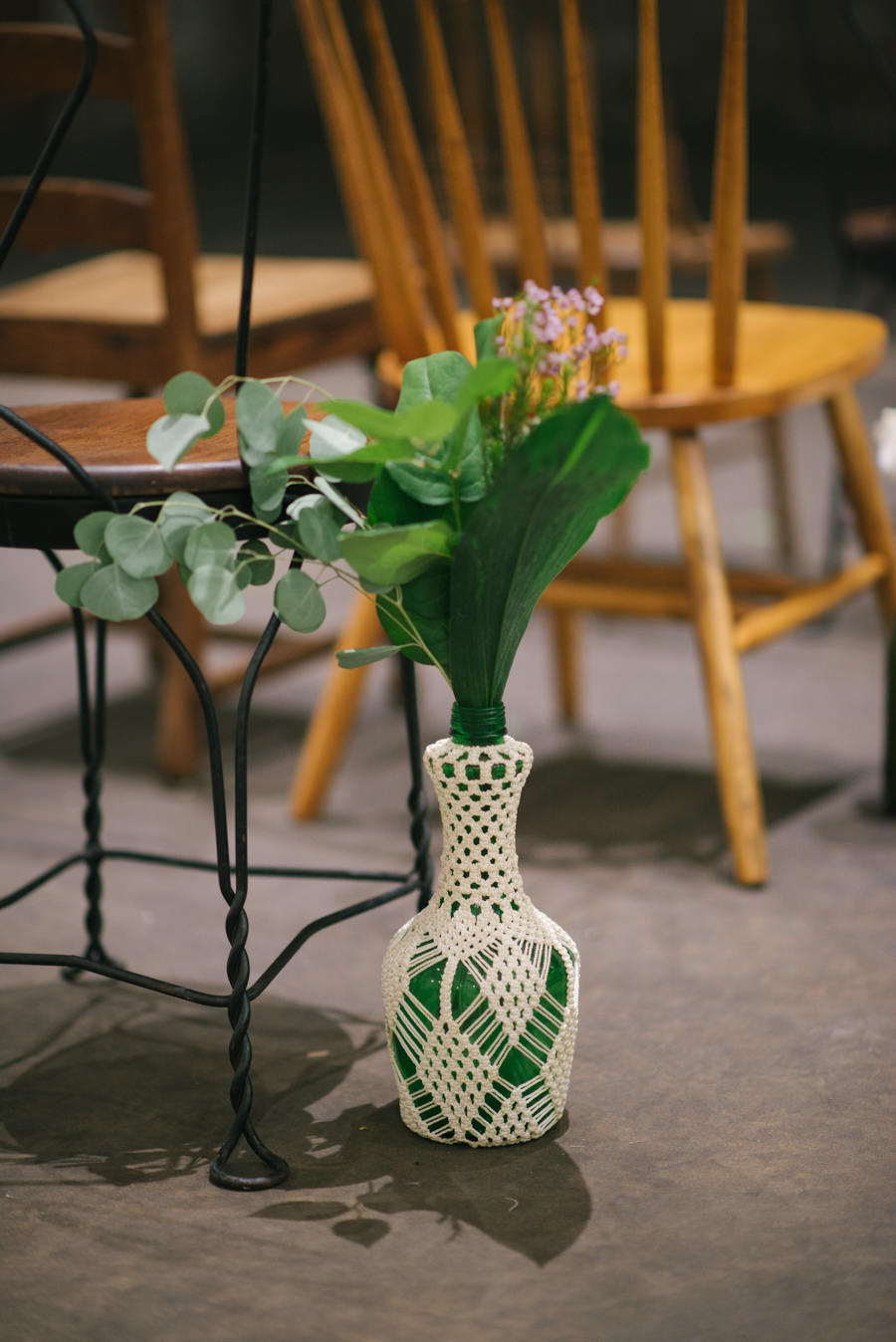 Wedding Ceremony Vintage Vase with Crochet Cover and Greenery with Mis-Matched Wooden Chairs