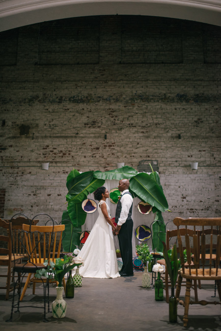Eco-Friendly Wedding Arch of Palm Leaves with Wedding Tropical, Carribean Ceremony Vases with Crochet Detail and Greenery with Wooden Chairs