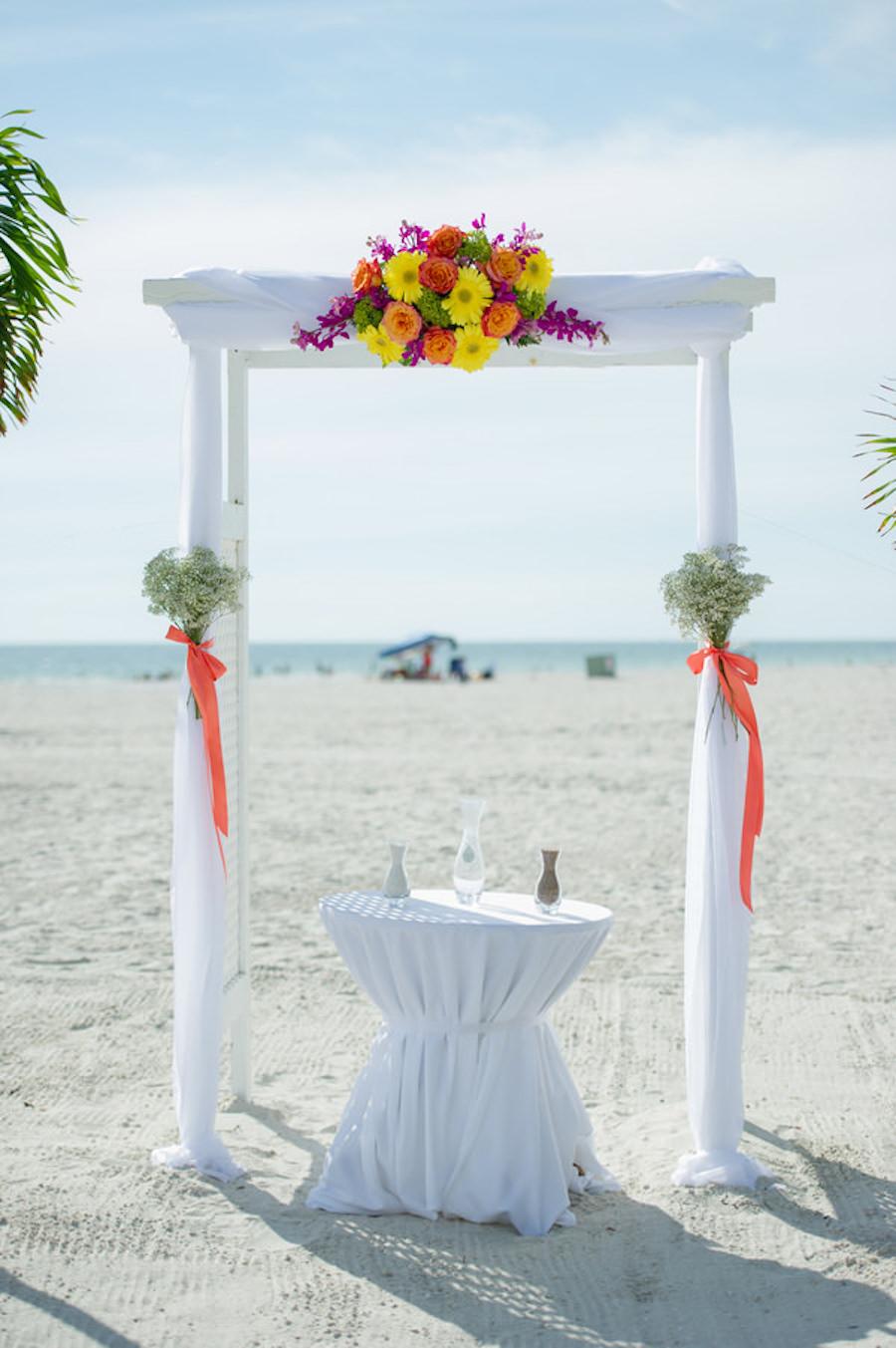 St. Pete Beach Wedding Ceremony Decor with White Wedding Altar with Bright Yellow, Orange and Purple Flowers  St. Pete Wedding Photographer Andi Diamond Photography