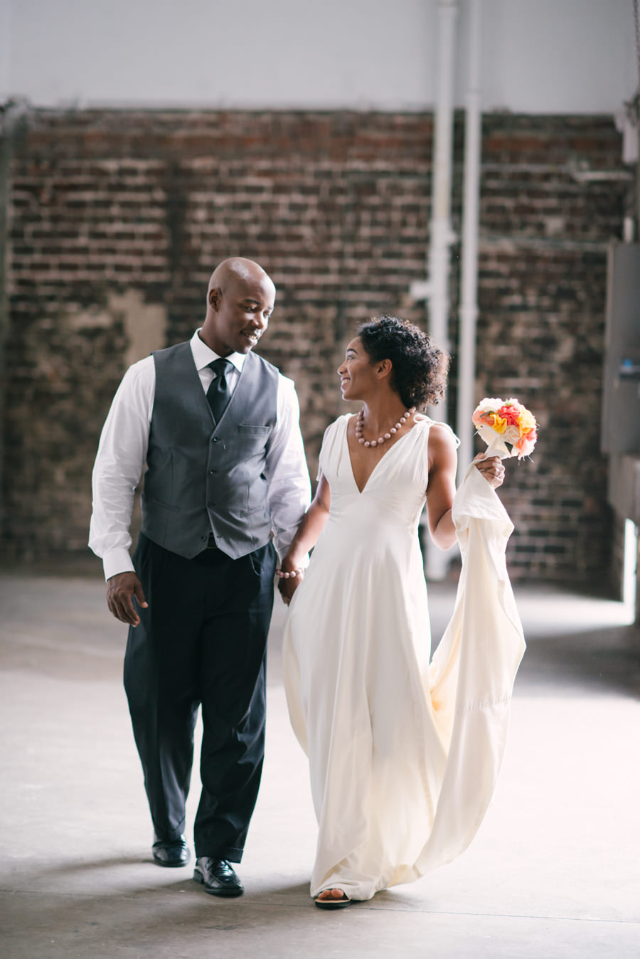 Wedding Day Portrait of Bride in Sheath Ivory Wedding Gown with Groom in Grey Vest