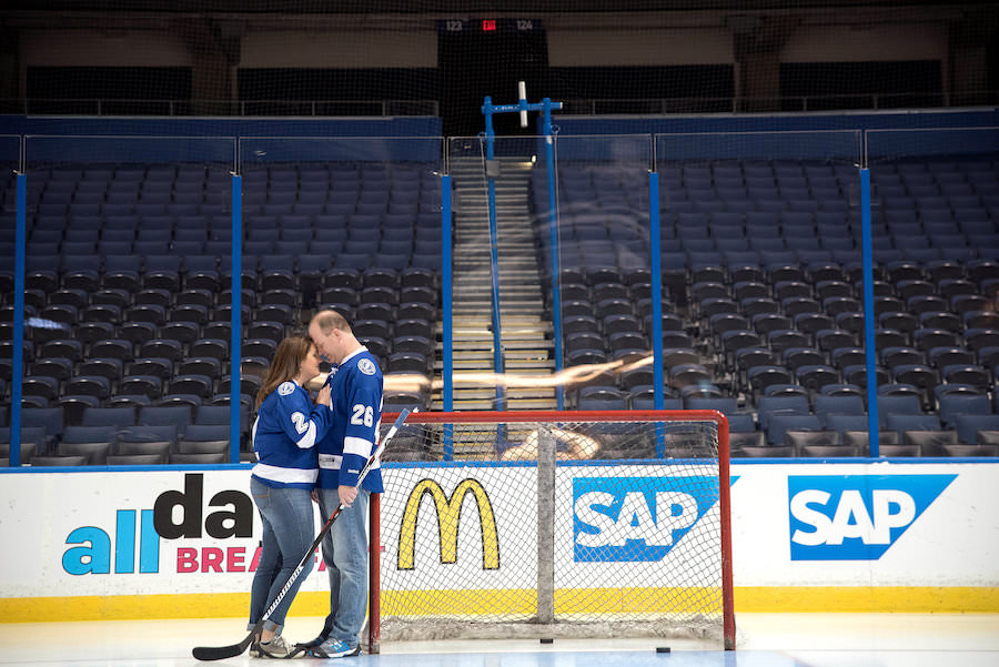 Tampa Lightning Themed Engagement Session at Amalie Arena with Hockey Jerseys, Sticks and Net on Ice | Kristen Marie Photography