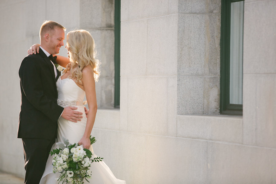 Outdoor, Downtown Tampa Bride and Groom Wedding Portrait in Black Tuxedo and Ivory, Strapless Sweetheart Hayley Paige Wedding Dress with Crystal Rhinestone Wedding Belt Sash | Tampa Hair and Makeup Artist Michele Renee The Studio