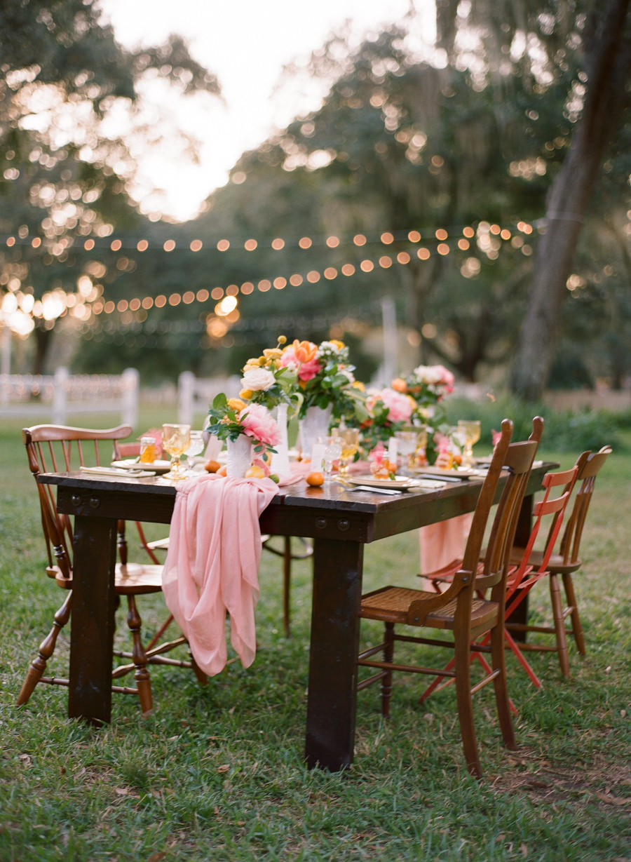 Outdoor Wedding Reception Decor with Vintage, Mis-Matched Wooden Chairs and Orange, Yellow and Pink Wedding Centerpieces with Cafe Lighting  Tampa Bay Rentals by Tufted Vintage Rentals