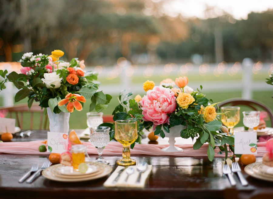 Outdoor Wedding Reception Decor with Vintage, White Vases, Citrus and Orange, Yellow and Pink Wedding Centerpieces on Wooden Farm Table   Tampa Bay Rentals by Tufted Vintage Rentals
