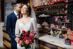 Bride and Groom Wedding Portrait | Mikaella Bridal Lace Wedding Dress with Sleeves holding Bright Pink and Red Wedding Bouquet | South Tampa Chocolate Pi Dessert Shop