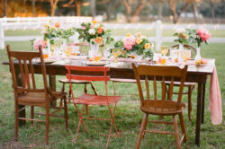 Outdoor Wedding Reception Decor with Vintage, Mis-Matched Wooden Chairs and Orange, Yellow and Pink Wedding Centerpieces with Cafe Lighting | Tampa Bay Rentals by Tufted Vintage Rentals