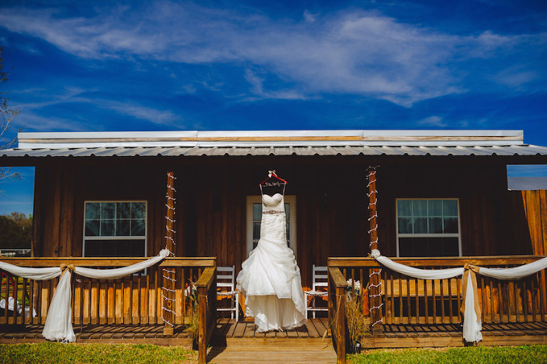 Ivory, Strapless Stella York Wedding Dress Hung on Wooden House | Plant City Wedding Venue Wishing Well Barn | Regina as the Photographer
