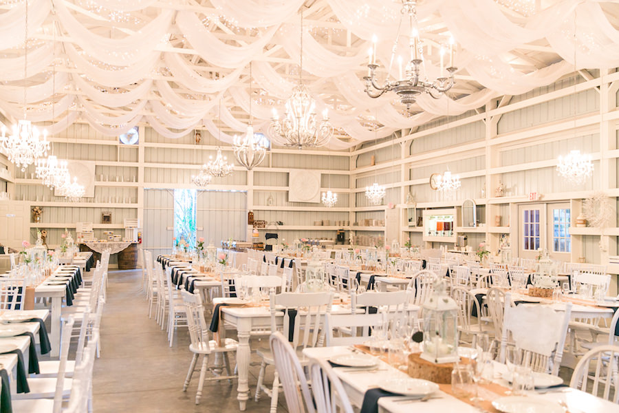 White Barn Wedding Reception with Long Feasting Tables, Rustic Chandeliers, Burlap Table Runners with Lace Accents, Natural Wood Rounds and White Lantern Centerpieces | Tampa Bay Wedding Venue Saxon Manor