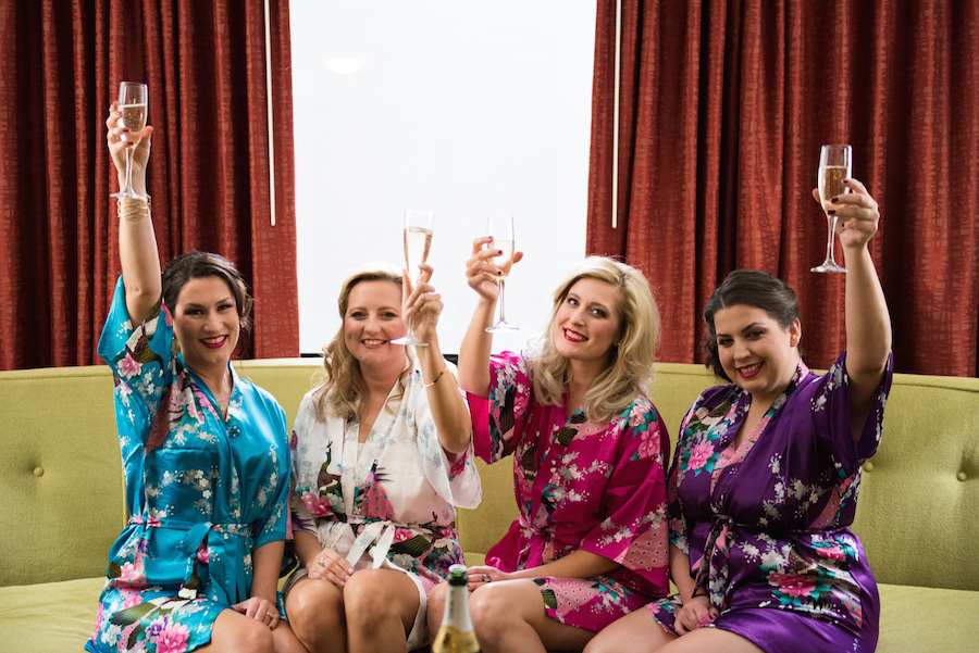 Getting Ready on Wedding Day: Bridesmaids in Matching Robes Drinking Champagne