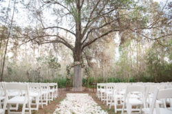 Rustic Outdoor Wedding Ceremony with Light Pink and White Floral Archway under Tall Pines with White Resin Folding Chairs and Rose Petal Aisle | Tampa Bay Wedding Planner Glitz Events