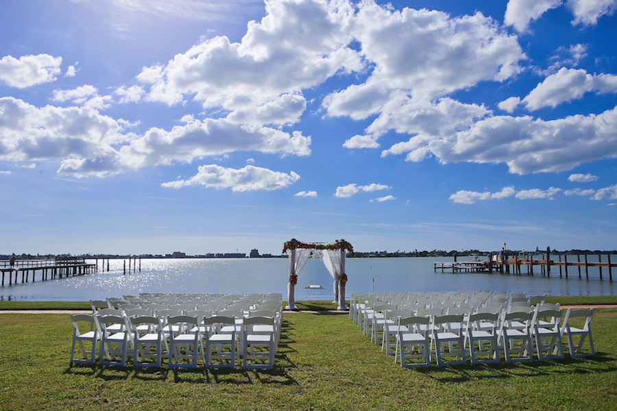 St Petersburg Waterfront Wedding Ceremony under Floral Arch with Tulle Overlay and White Resin Folding Chairs at Private Residence | Exquisite Events Wedding Planning