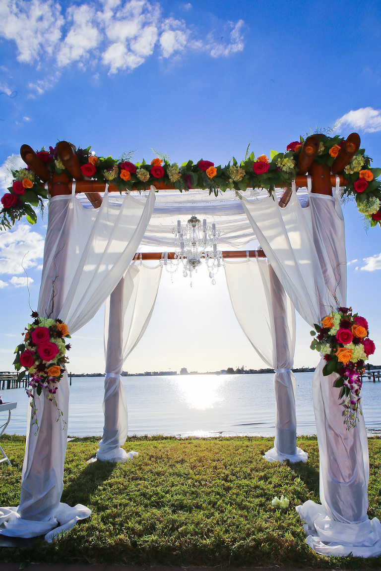 St Petersburg Waterfront Wedding Ceremony under Floral Arch with Fuchsia and Orange Roses, Greenery and Tulle Overlay | St. Petersburg Wedding Planner Exquisite Events