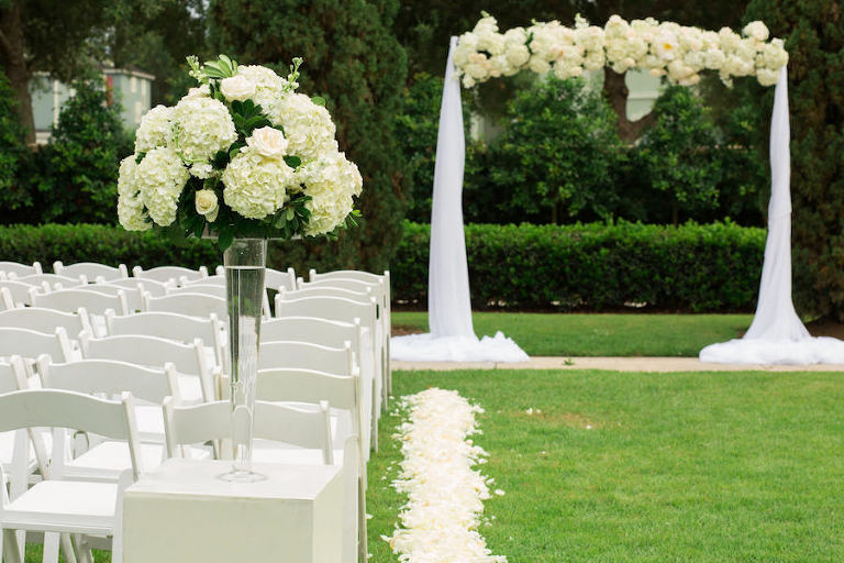 Outdoor Garden Wedding Ceremony With White Hydrangea And Tulle Arch Resin Folding Chairs