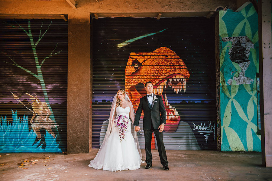 St. Petersburg Bride and Groom Wedding Portrait with Graffiti Backdrop in Ivory Strapless Sweetheart Wedding Dress and Cascading Purple and White Wedding Bouquet | Downtown St. Pete Wedding Florist Iza's Flowers