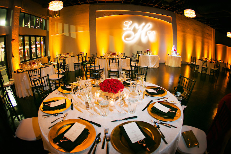 Tampa Wedding Reception Table Decor with Gold Chargers, Black Chiavari Chairs, and Red Rose Centerpiece and GOBO Monogram Lighting