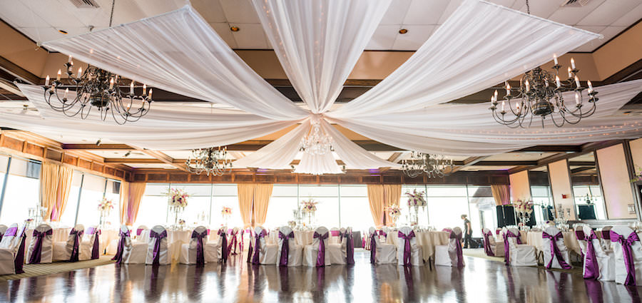 Indoor, Waterfront Tampa Wedding Reception Tabe Decor with Ceiling Drapery and Purple Bow Chair Sashes