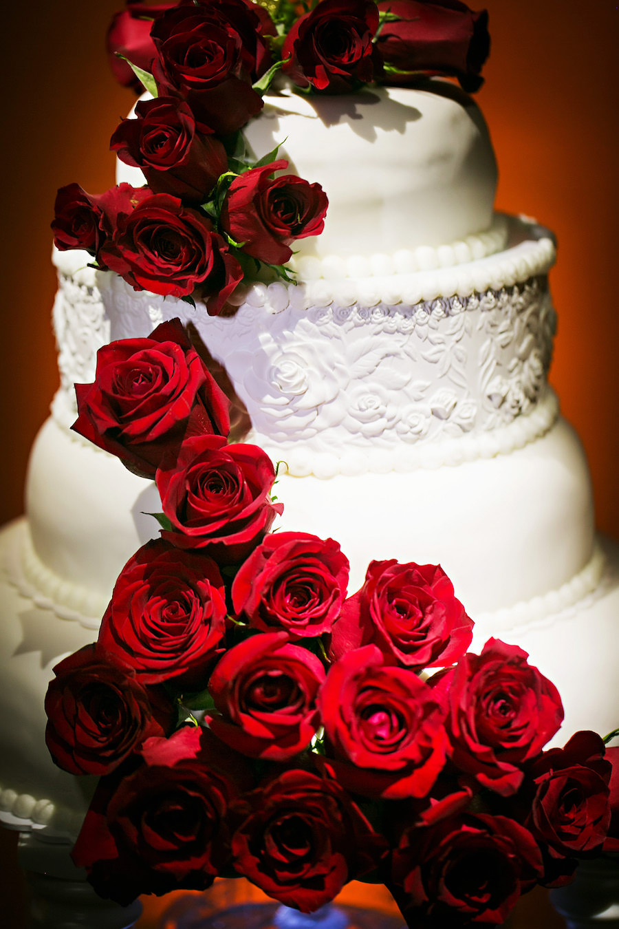 Four tiered, Round, White Wedding Cake With Red Cascading Roses