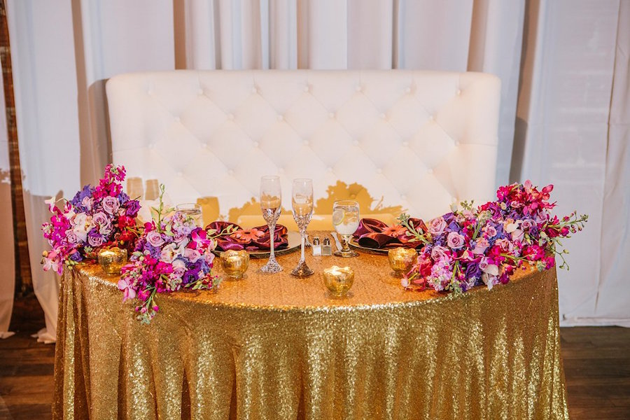 Bride and Groom Sweetheart Table with Purple and Fuchsia Wedding Centerpieces on Gold Sequin Specialty Linens | St. Petersburg Wedding Planner Exquisite Events | Flowers by Iza's Flowers | Purple and Gold Wedding Decor Ideas