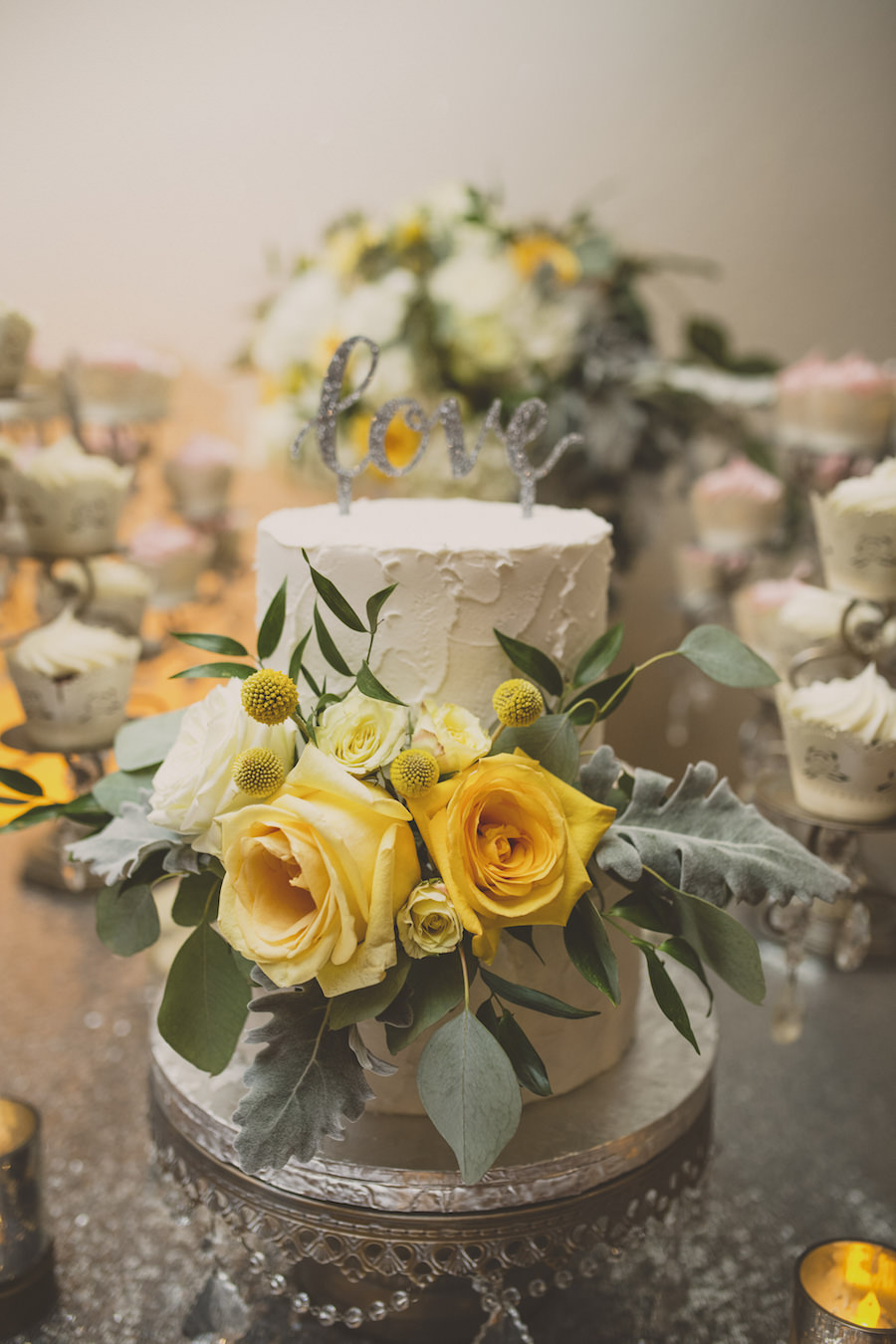 Two Tier Round White Wedding Cake with Yellow Roses and Greenery on Silver Cake Stand with Love Cake Topper